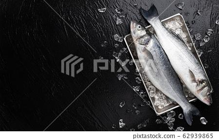 Seabass fish on metal tray on black stone background 62939865