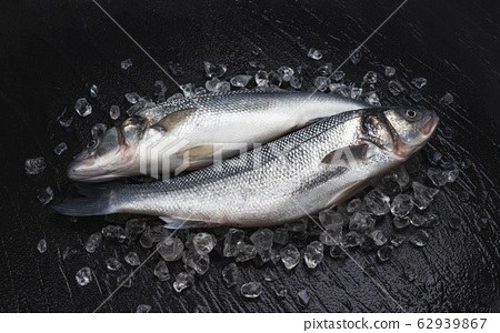 Fresh seabass fish on ice on black background 62939867