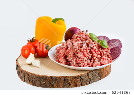 fresh raw minced beef in a plate close up on a rustic wooden cutting board, with peppers, onion and tomatoes 62941868