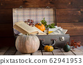 Autumn composition, autumn mood, pumpkin and book on wooden table. 62941953