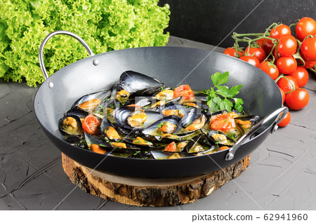 Italian mussels from Taranto on a pan with tomatoes and salad 62941960