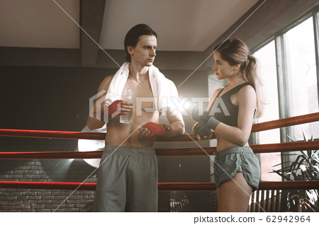 Portrait of a couple of boxers having a good time during training in a boxing gym and smiling 62942964