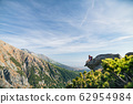 Mature man with backpack hiking in mountains in summer, resting. 62954984