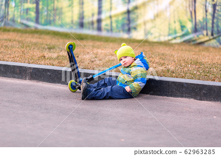 Cute little boy falling off his scooter 62963285