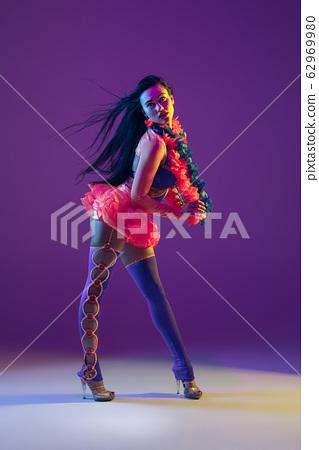 Attractive hawaiian brunette model on purple studio background in neon light 62969980