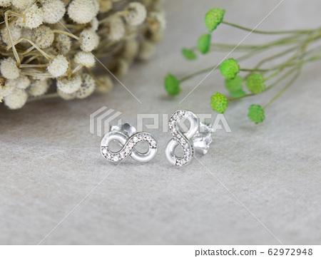 A pair of beautiful diamond earrings in the infinity shape 62972948