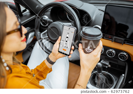 Woman controlling car with a smart phone 62973762