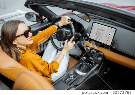 Woman driving sports car with a digital touchscreen 62973765