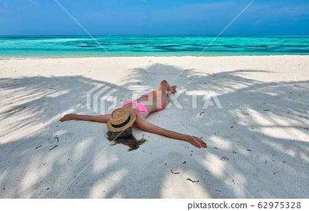 Woman in bikini at tropical beach under the palm 62975328