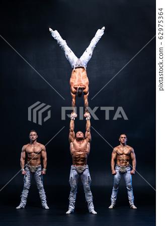 Four muscular man perform difficult acrobatic tricks on black studio  62975364