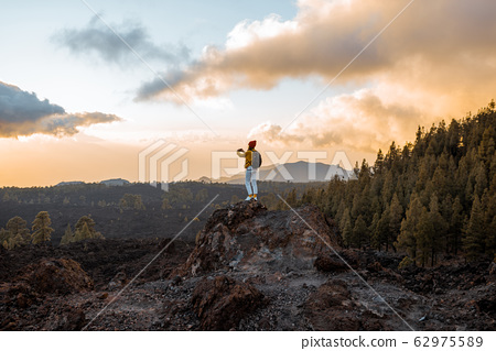 Woman traveling on the volcanic land on a sunset 62975589