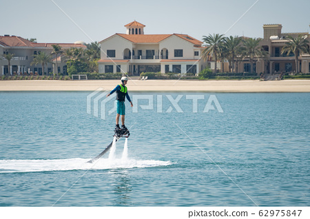 Water extreme sport. The guy is flying at the aquatic flyboard. Extreme rest on the sea 62975847