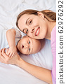 Young adult woman cuddle to her little newborn offspring 62976292