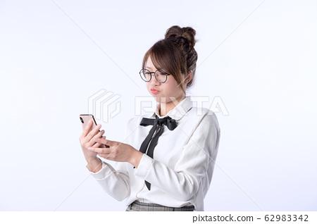 年輕亞洲女孩嘟著嘴看著智慧型手機亞洲, 東方, 日本, 台灣, 韓國, 年輕, 女性, 女孩, 套裝 62983342