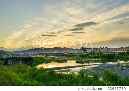 在河面上,太陽在天際線升起,而宮彩彩(Aya Miyabi)在水面上反射。 62985720