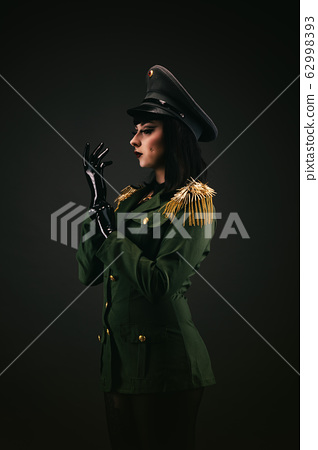 Portrait of a young woman in uniform, wearing latex gloves 62998393