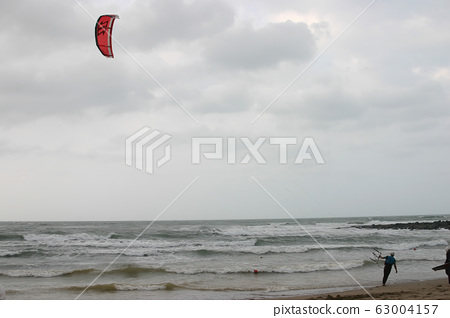 People playing Kitesurfing on a storm day 63004157