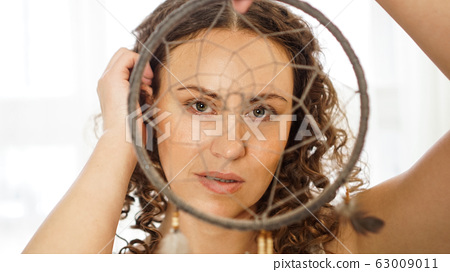 Woman with curly hair with a dream catcher in hand 63009011