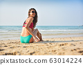 Woman in a sexy bikini wear sunglasses at the 63014224