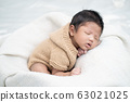 Happy cute adorable Asian baby boy with black hair lying on a white blanket. 63021025