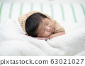 Adorable newborn baby peacefully sleeping on a white blanket. 63021027