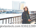 Asian pregnant women tourist holding a phone Standing by the river. 63022289