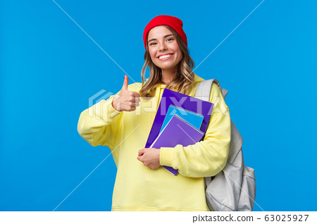 Sounds good. Cheerful cute and smart caucasian girl in red beanie studying hard for exams, encourage student keep up, show thumbs-up in like or approval, hold notebook and backpack 63025927