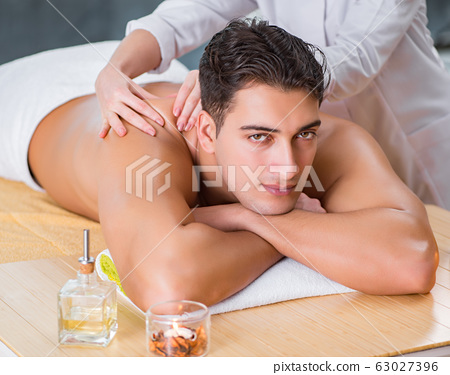 Handsome man during spa massaging session 63027396