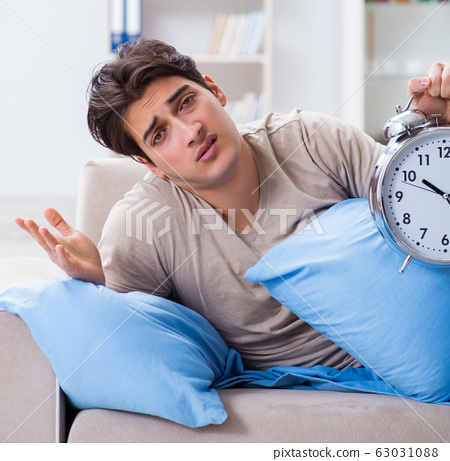 Man having trouble waking up with alarm clock 63031088