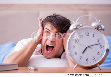 Man in bed frustrated suffering from insomnia with an alarm cloc 63033757