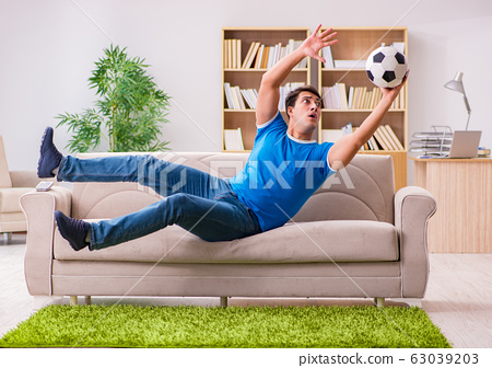 Man watching football at home sitting in couch 63039203