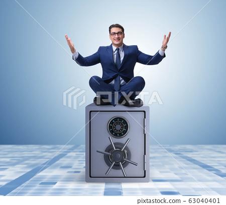 Businessman resting putting leg on safe 63040401