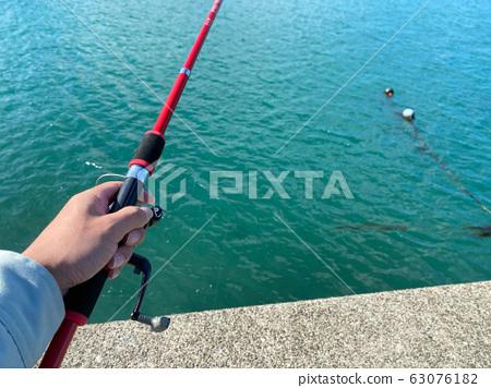 在防波堤上釣魚。 63076182