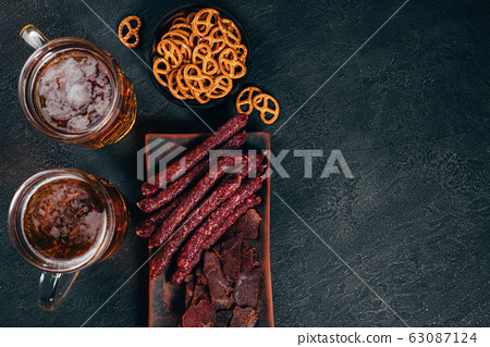 Sausages and pretzels with two mugs of lager 63087124