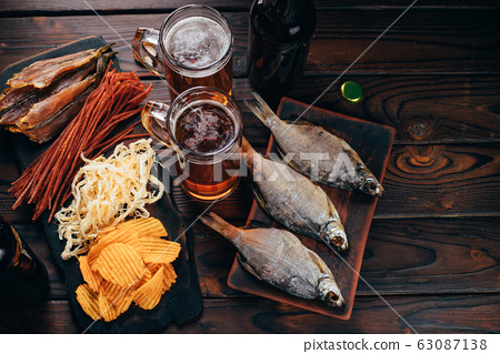 Two mugs of lager and selection of beer snacks 63087138