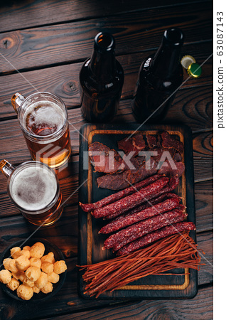 Two mugs of lager and selection of beer snacks 63087143