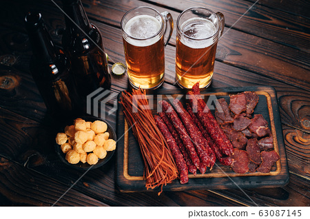 Two mugs of lager and selection of beer snacks 63087145