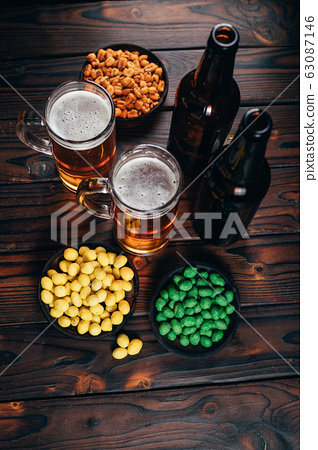 Appetizing snacks with two mugs of light beer 63087146