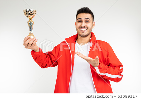 man in a red tracksuit shows off the winner's gold cup on a white background 63089317