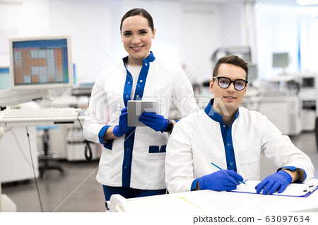 Smiling research scientists working in modern science lab 63097634