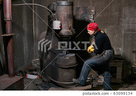 woman blacksmith processes a hot workpiece with a 63099134