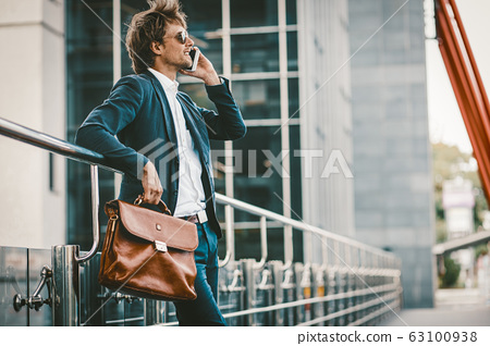 Young man in a sute standing outdoors and talking on the mobile phone and smiling 63100938