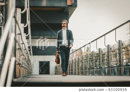 Young ambitious businessman walking out of the business center 63100939
