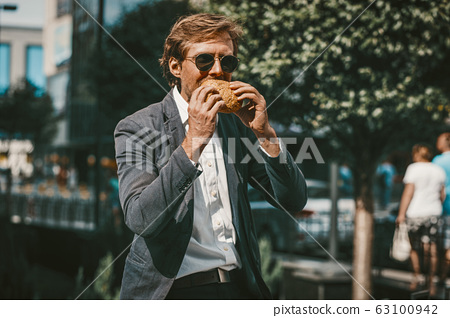 Young freelancer businessman eating a hamburger outside on a street 63100942