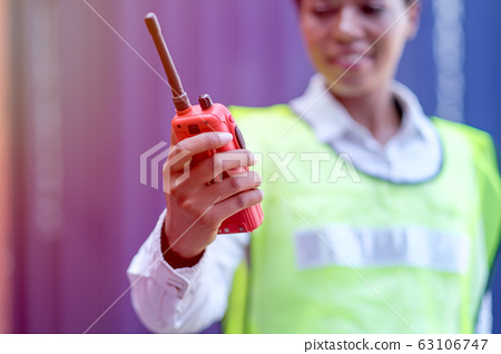 Hand of technician woman hold and shows red walky-talky in cargo container area 63106747