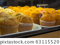 Assorted muffins arranged on tray at bakery shop. 63115520