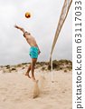 Young man playing volleyball on summer beach 63117033