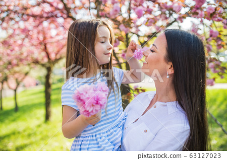 Young mother holding small daughter outside in spring nature. 63127023