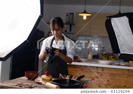 photographer food , asian women is taking pictures of food her food in studio. 63129294