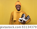 African guy in hat and scarf, holds skates in his hands smiling at camera 63134379